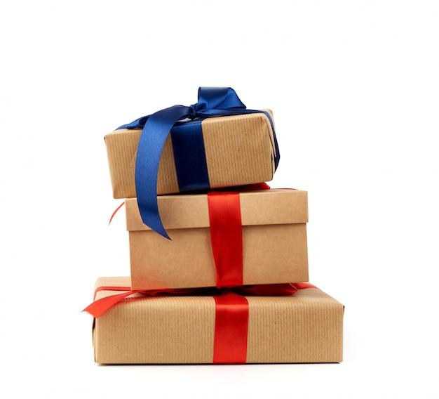 茶色のクラフトペーパーに包まれ、絹の青と赤のリボンで結ばれた贈り物のスタック