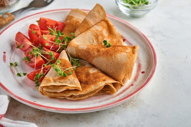 하얀 접시에 체리 토마토와 아루굴라 마이크로그린을 곁들인 글루텐이 없는 메밀가루 크레페 팬케이크를 쌓고, 아침 식사로 홈메이드 건강한 베이킹을 합니다. 조롱. 공간을 복사합니다.