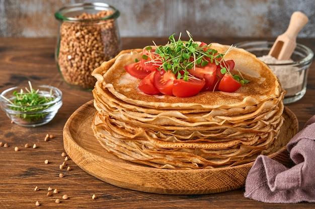 글루텐이 없는 메밀가루 크레이프 팬케이크를 나무 접시에 체리 토마토와 아루굴라 마이크로그린과 함께 쌓고, 아침 식사로 홈메이드 건강한 베이킹을 합니다.