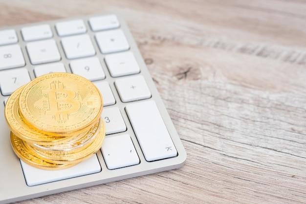 Стек золотых биткойнов на белой клавиатуре