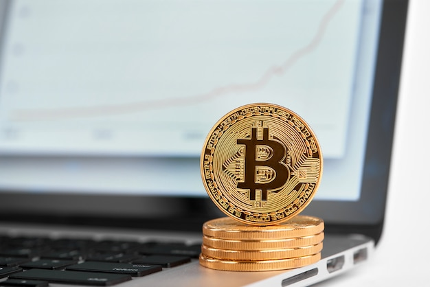 Стог золотых биткойнов с одним биткойном на его краю стоя на компьтер-книжке с финансовой диаграммой на его экране.