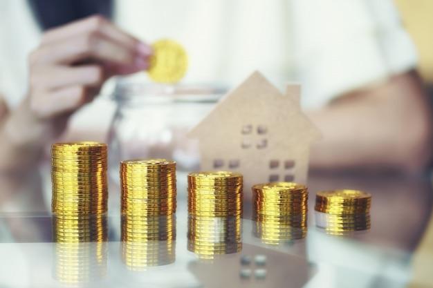 Стек золотых монет с деревянным домом