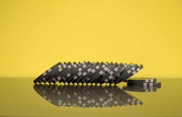 金色の背景に灰色のカジノチップのスタック