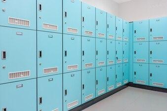 Stack of green metal school lockers with combination locks and doors shut