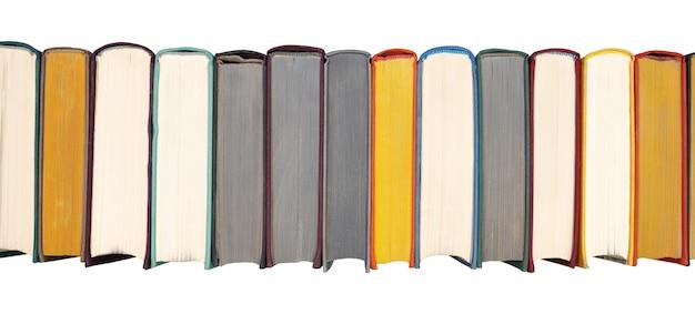 白い背景で隔離のハードカバーの本の本棚のクローズアップビューにハードカバーの本のスタック