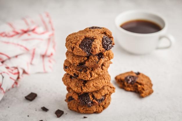 白い背景の上のチョコレートと健康的なビーガンクッキーのスタック。きれいな食事のコンセプト。