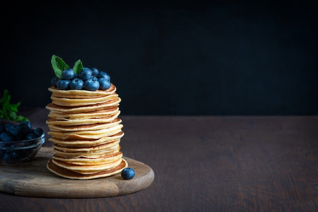Стопка домашних американских блинов со свежей черникой и мятой на темном деревянном столе