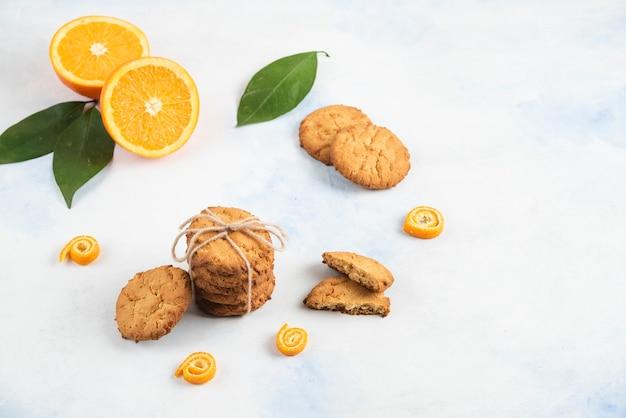 흰색 표면에 오렌지와 잎이 있는 집에서 만든 쿠키를 쌓으세요.