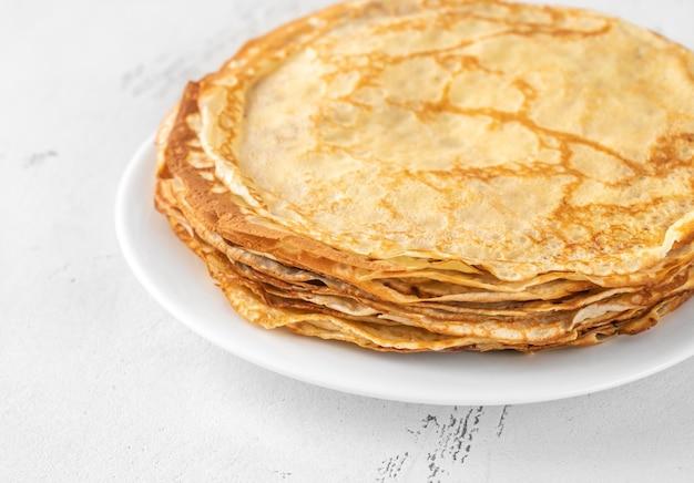 Стек домашних блинов на белой тарелке