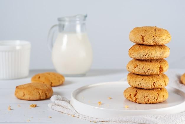 白い背景の上の牛乳の水差しと自家製ゴールデンブラウンコーンクッキーのスタック