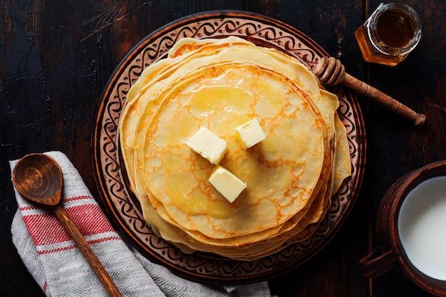 Стек домашних тонких блинов с кусочками масла и меда на старой деревенской керамической тарелке. вид сверху.