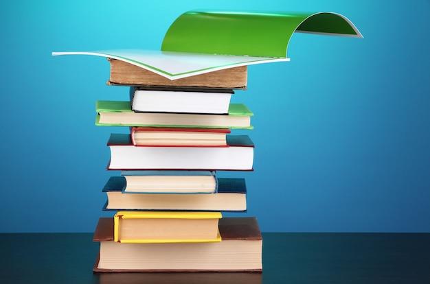 파란색 표면에 나무 테이블에 흥미로운 책과 잡지의 스택