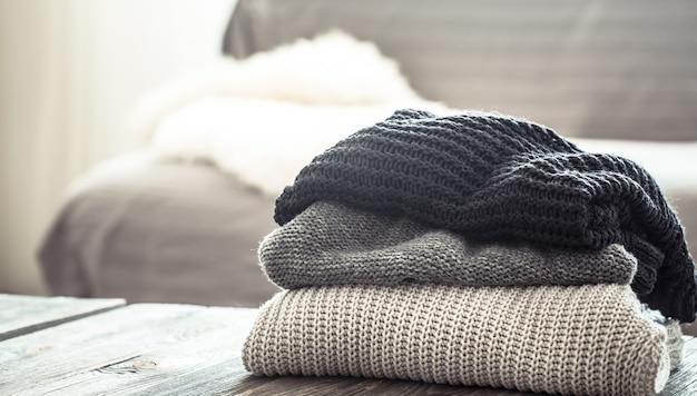 Стопка вязаных свитеров на деревянном столе