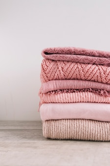 Stack of knitted sweaters on floor
