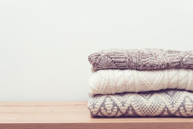 木製の背景にニットの暖かい服のスタック。テーブルの上のセーターの山。秋冬シーズンのニットウェア。