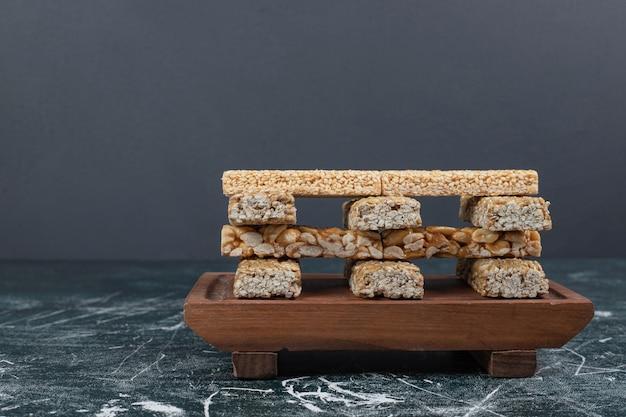 Стек сладостей козинаки с семенами и орехами на деревянной тарелке. фото высокого качества