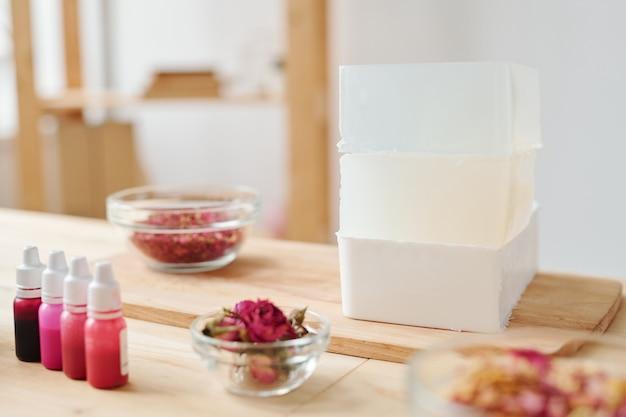 Стопка больших и толстых кусков твердой мыльной массы на деревянной доске с цветами в пластиковых бутылках и ароматическими ингредиентами в мисках рядом