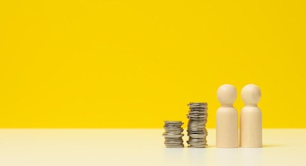 白いテーブルの上に金属のコインと男性の木製の数字のスタック。貯蓄と経費、家計、州からの補助金、コピースペース