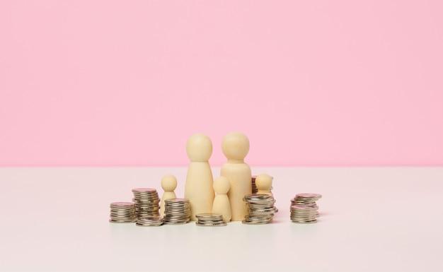 白いテーブルの上に金属のコインと男性の木製の数字のスタック。貯蓄と経費、家計、州からの補助金