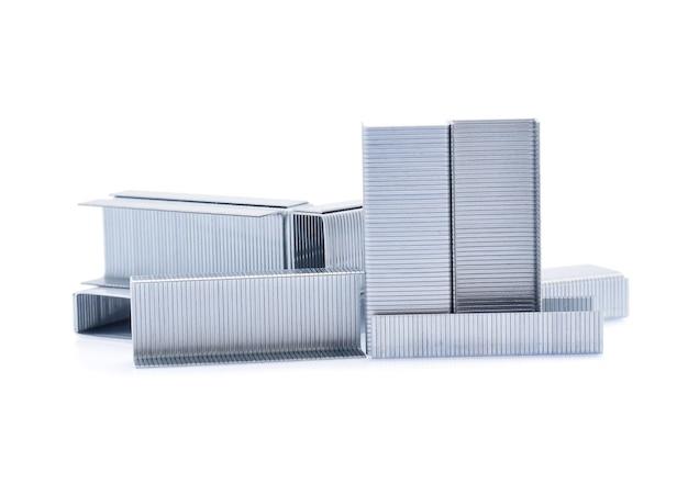 白で隔離される金属ステープルのスタック。
