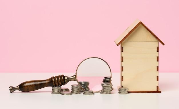 분홍색 배경에 금속 화폐와 돋보기 및 목조 주택의 스택. 부동산 임대, 구매 및 판매 개념입니다. 부동산 서비스, 건물 수리 및 유지 보수