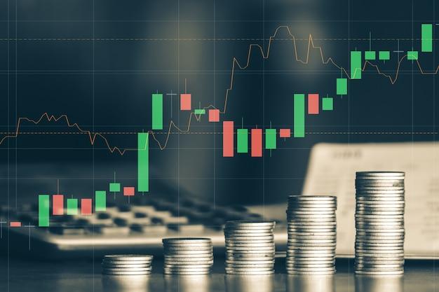 Стек денежная монета на столе с торговым графиком бизнес и финансовая концепция