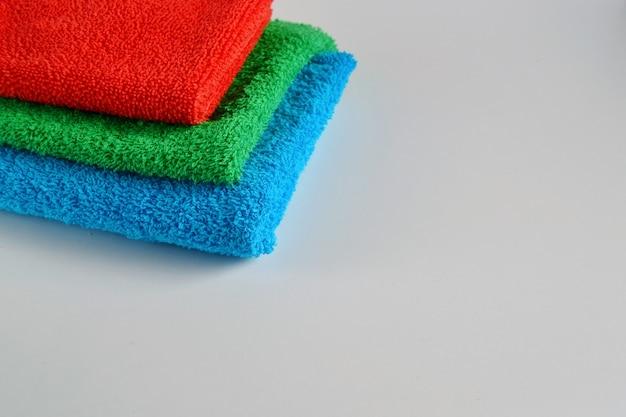 Стопка разноцветных гостиничных полотенец на светлом фоне