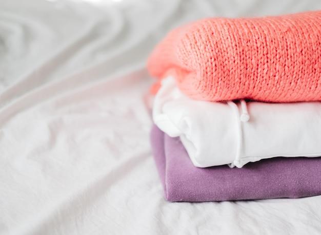 Стек разноцветной одежды на белой кровати из шкафа.
