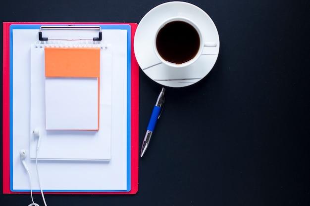 Стек ноутбуков и буфер обмена рядом с ручкой и кофе