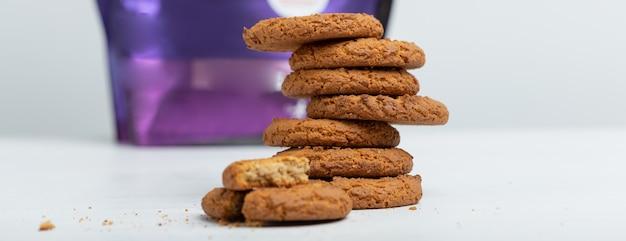 오트밀 쿠키의 스택은 흰색 테이블에 단백질 패킷의 배경에 놓여 있습니다. 스포츠 영양 개념.