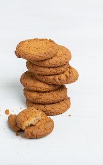 Стек овсяного печенья лежит на белом столе. концепция низкокалорийных десертов и здоровых закусок. сладкая кулинария.