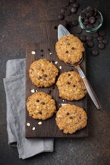 초콜릿과 어두운 녹슨 콘크리트 또는 돌에 부스러기와 오트밀 쿠키의 스택.