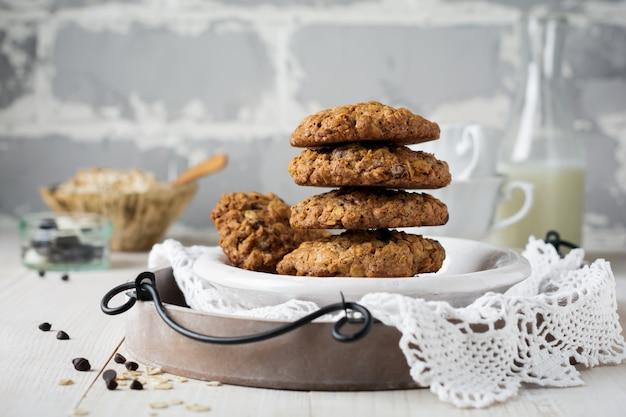 부스러기와 우유 병 빛에 초콜릿 오트밀 쿠키의 스택.