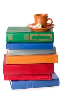 Стек старых книг и чашка кофе, изолированные на белом фоне