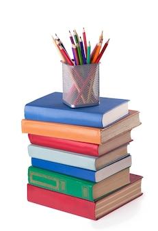 Стек старых книг и цветные карандаши, изолированные на белом фоне