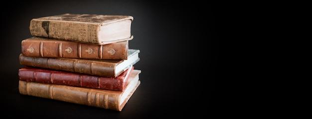 黒の背景バナーに分離された古い本のスタック