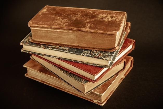 오래 된 검은 배경에 고립 된 책 스택
