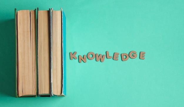 木製の文字の単語の知識を持つ古い本のスタック