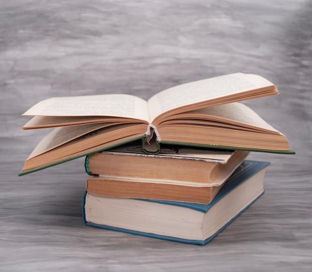 灰色の背景に黄色のページを持つ古い本のスタック
