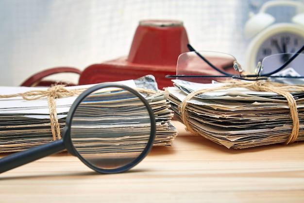 Стек старых фотографий, очки, лупы, фотоаппараты и будильник на деревянном столе