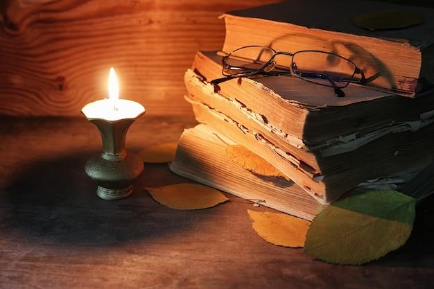 木製のテーブルに古いボロボロの本のスタックは、キャンドルとグラスに火をつけた