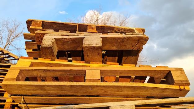 Стек старых использованных деревянных поддонов на открытом воздухе на складе предприятия по доставке грузов на фоне облачного неба, вид сверху