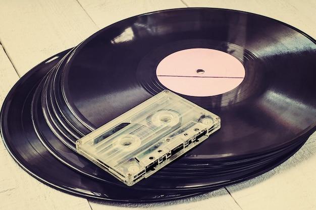 白い木製のテーブルに古いビニールレコードとオーディオカセットのスタック。トーンの写真