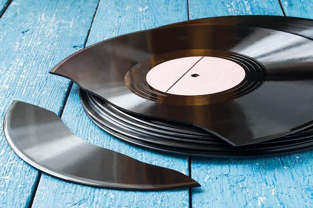 青い木製の背景に古いビニールレコードのスタック1つのレコードが壊れています