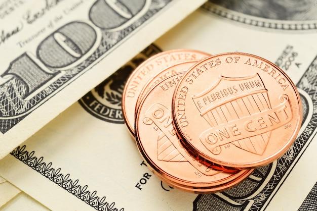Стек монет сша в один цент с несколькими стодолларовыми купюрами