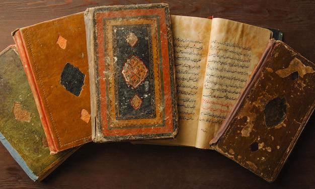アラビア語で開いている古代の本のスタック。古いアラビア語の写本とテキスト。上面図