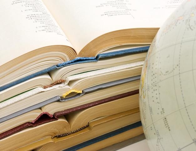 開いた本と白で隔離されるグローブのスタック