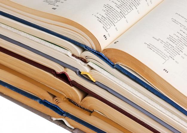 空白に分離された開いた本のスタック