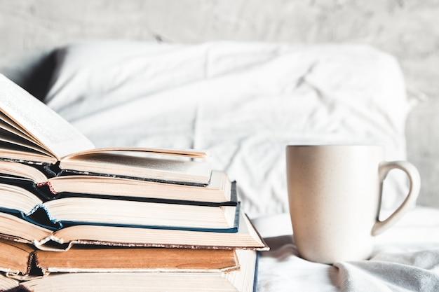 ベッドで一杯のコーヒーと開いた本のスタック