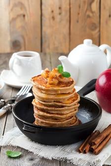 古い木の表面に焼きりんごとシナモンとそば粉からのパンケーキのスタック。選択的な焦点。